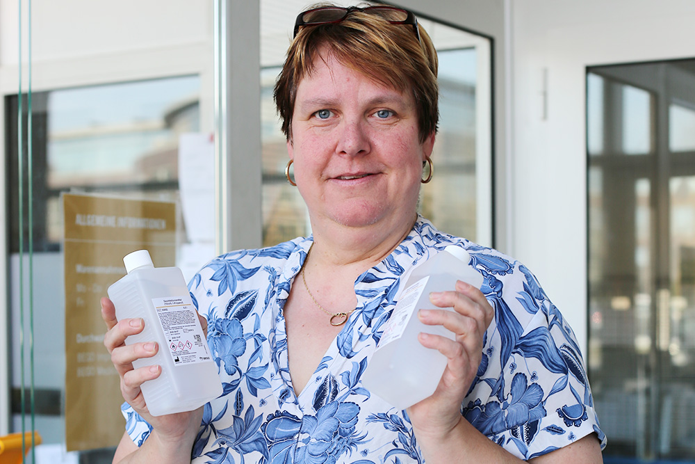 Sabine Metschies, quality management and quality assurance employee in the BEGO material production, is pleased to hand over the disinfectants produced by BEGO to interested companies from the Technology Park Uni Bremen.
